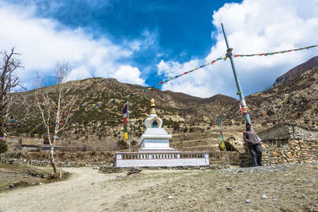 Mountain village in the Himalayas, Nepal-05042018: Great white stone Buddhist stupa April 5, 2018 in the mountain village in the Himalayas, Nepal. Фото со стока