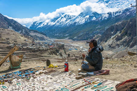 Manang village in the Himalayas, Nepal-04052018: an Elderly man sells local Souvenirs on April 5, 2018 in the mountain village of Manang in the Himalayas, Nepal.