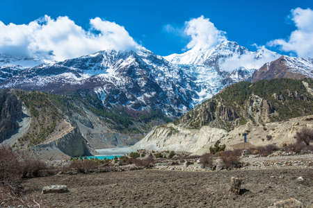 A small emerald lake near the village of Manang, Nepal. Beautiful snowy mountain peaks and clouds in the Himalayas.