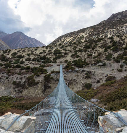 Long metal suspension bridge over the river in the Himalayas, Nepal.