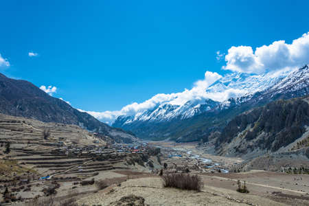 View of Manang village in Himalayas, Nepal. Beautiful snowy mountain peaks and clouds.