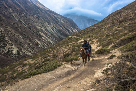 Mountain trail in the Himalayas, Nepal-05.04.2018: Two men riding on April 5, 2018 on a mountain trail in the Himalayas , Nepal.