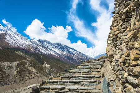 Stone stairs leading to the sky in the Himalayas, Nepal. Beautiful snowy mountain peaks and clouds.
