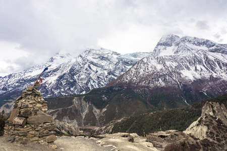 Stone Buddhist stupa against snowy peaks and clouds in the Himalayas, Nepal.