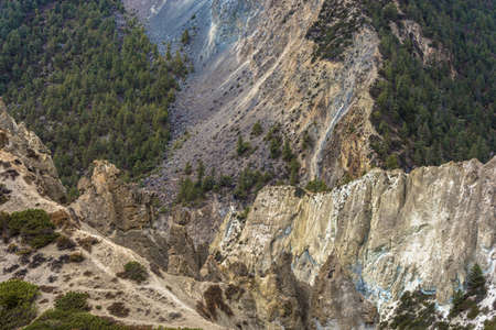 Original rocks against a coniferous green forest in the Himalayas, Nepal.