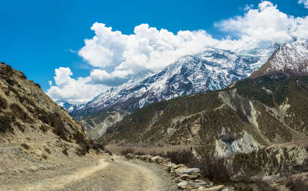 Mountain trail in the Himalayas on a Sunny spring day, Nepal. Beautiful snowy mountain peaks and clouds. Фото со стока