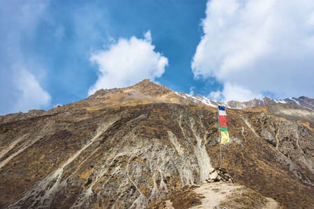Small stupa, built of stone with a flag on the background of a snowy peaks in the Himalayas, Nepal.