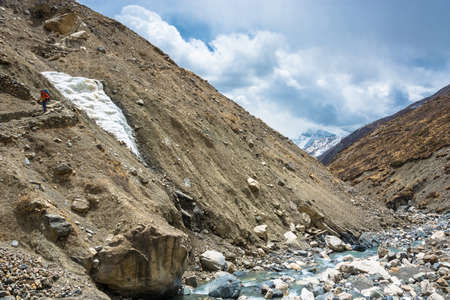 Trek around the Annapurna, Nepal - 04062018: a Lonely hiker on the mountain path 6 April 2018 at the track around Annapurna, Nepal. Фото со стока
