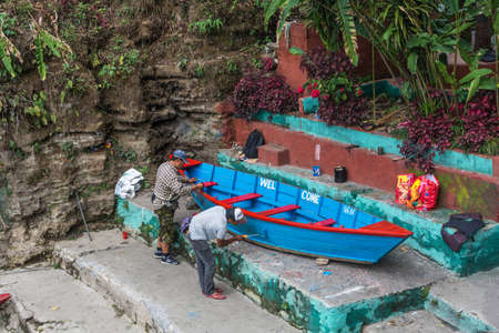Pokhara, Nepal-11.04.2018: Two workers paint a wooden boat on 11 April 2018 Pokhara, Nepal.