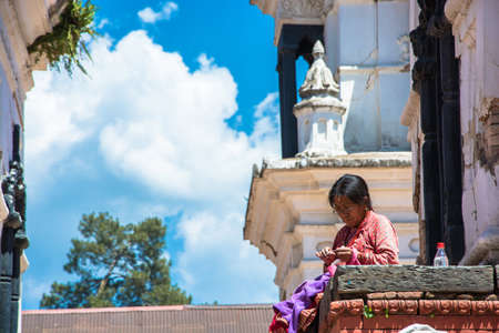 Kathmandu, Nepal - 04042018: an Old woman sewing clothes in the temple complex Pesonalised 13 April 2018, Kathmandu, Nepal.