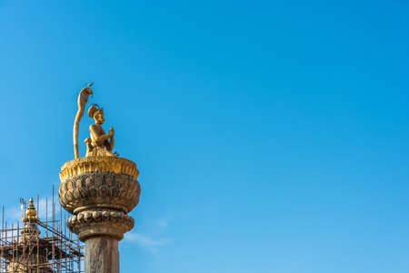 Original decoration on top of Buddhist temple on blue sky background, Nepal.