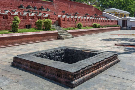 Square stone pit covered with a black soot in the complex Pashupatinath Temple, Nepal. Stock Photo - 106570668