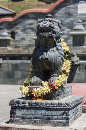 Buddhist sculpture with a large wreath of flowers in the complex Pashupatinath Temple, Nepal. Stock Photo - 106570652