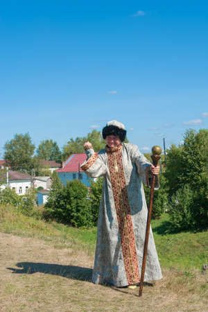 Luh, Ivanovo region, Russia - 08252018: Woman in Russian clothes and with a staff at the regional festival-fair Luk-luchok August 25, 2018 in the city of Luh, Ivanovo region, Russia.