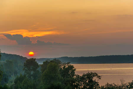 Bright yellow disk of the setting sun against the background of the cloudy sky and green trees on the bank of the Volga River.