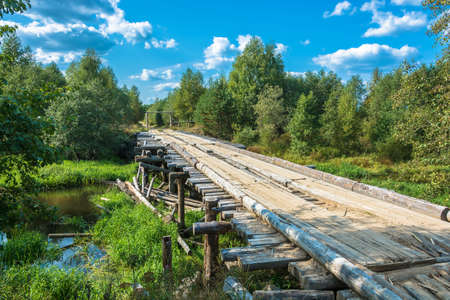 A wooden bridge across a small river in a summer sunny day.