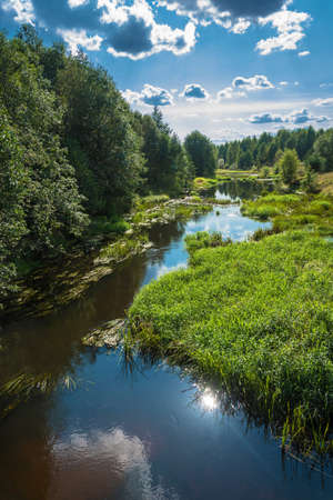 A beautiful summer landscape with a small river and a reflection of the sun in the water.