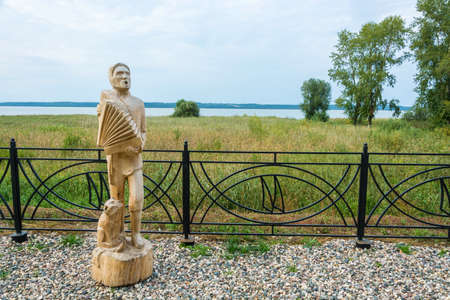 Galich, Kostroma Region, Russia - 11.09.2018: Wooden sculpture of a musician playing the accordion on the Galichsky Lake embankment September 11, 2018, Galich, Kostroma Region, Russia.