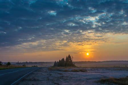 Beautiful sunrise in the open area with hazy haze and cloudy sky. Фото со стока