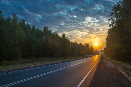 Asphalt road in the bright rays of the rising sun with a beautiful cloudy sky.