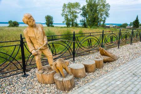 Galich, Kostroma Region, Russia - 11.09.2018: Wooden sculpture of a fisherman on the Galichsky Lake embankment September 11, 2018, Galich, Kostroma Region, Russia. Редакционное