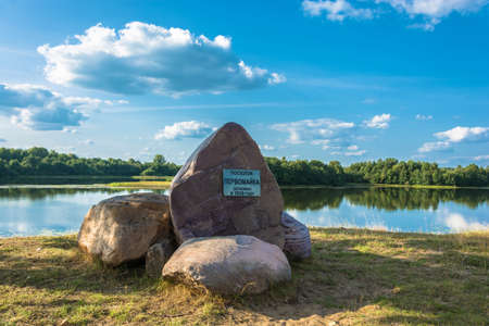 Huge stones on the river bank. The inscription on the plate: The village of Pervomayka was founded in 1929.