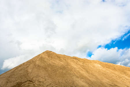 A large mountain of yellow sand, illuminated by the sun against the cloudy sky. Фото со стока