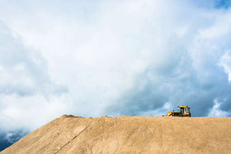Yellow bulldozer on a large hill of sand on the background of the cloudy sky. Фото со стока