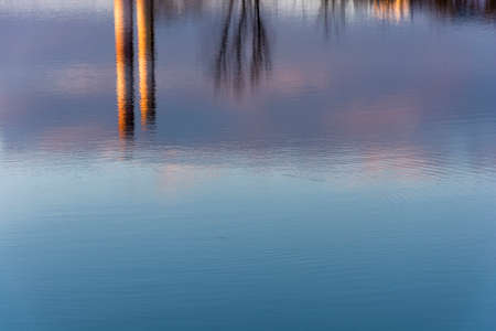 Beautiful reflection of trees and tall pipes in the blue mirror surface of the river. 版權商用圖片