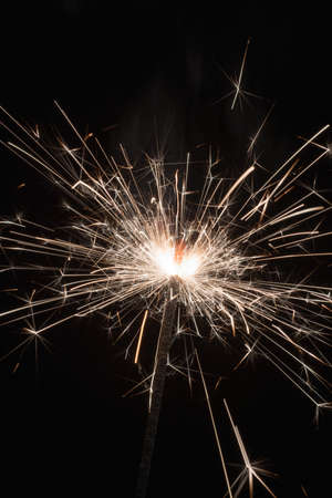 Close-up of bright sparkles of bengal fire on a black background.