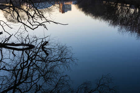Beautiful reflection of trees and high-rise building in the blue mirror smooth surface of the river.