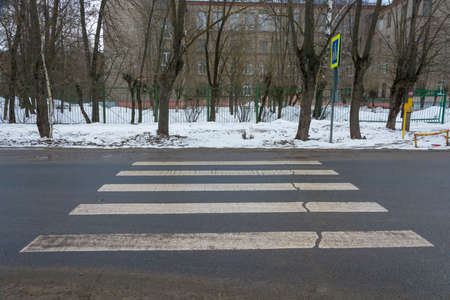 Incorrectly designed pedestrian crossing on an asphalt road, resting on a snow drift.
