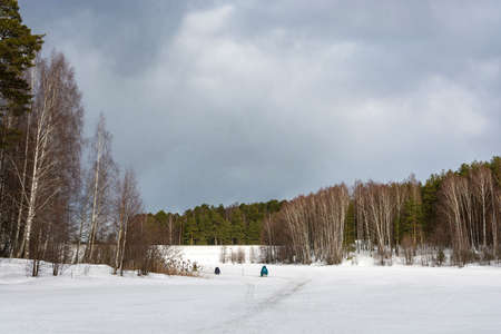 Three fishermen on the ice of a small river on a cloudy spring day, Russia.