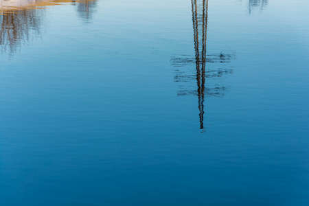 Beautiful reflection of the power line in the blue mirror smooth surface of the river.