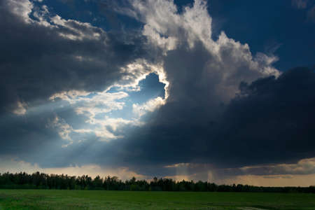 Beautiful landscape with thundercloud and sunshine over a green field on a spring day.