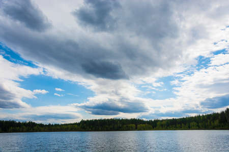 Beautiful cloudy sky over a small lake with a wooded shore on a spring day.