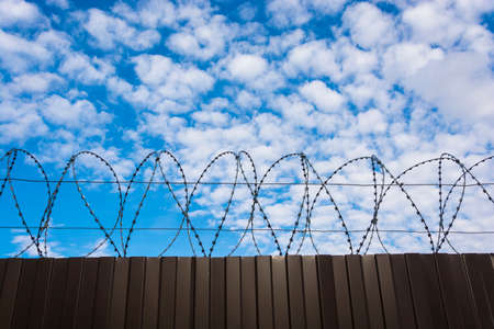 Metal fence from a sheet profile with barbed wire against the background of a beautiful cloudy sky.