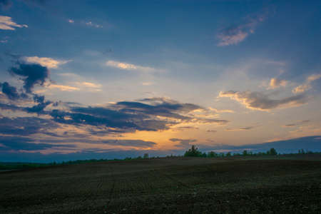 Beautiful bright sunset over a large plowed field in the spring evening. Stok Fotoğraf