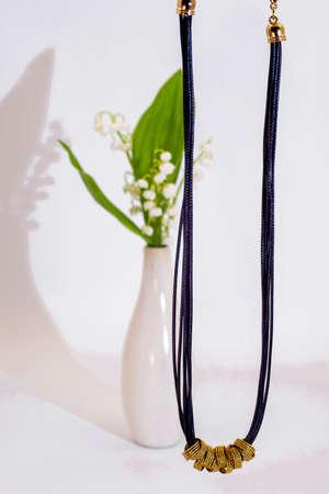 White necklace on white background.