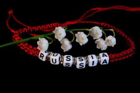 Red lace charm bracelet and white lily of the valley flower on a black background.