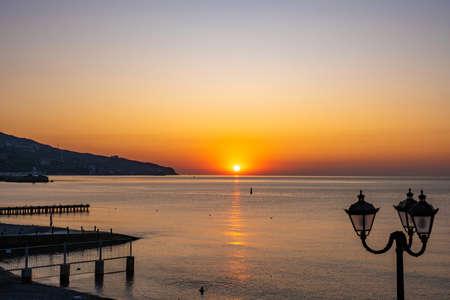 Beautiful sunrise over the calm Black Sea in Yalta, Crimea.
