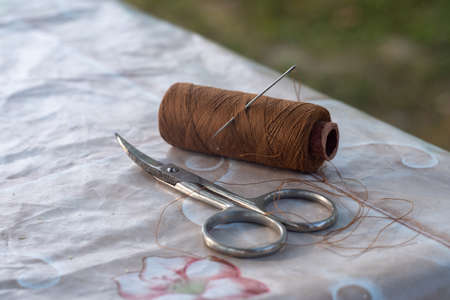 Small scissors and a sewing needle with a spool of brown thread, taken in close-up. Фото со стока