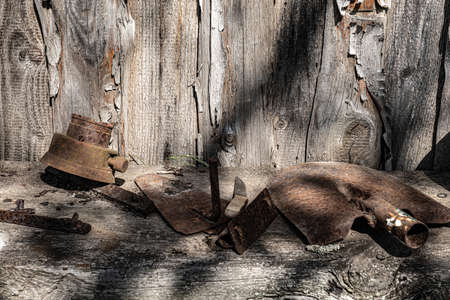 An old rusty shovel and other metal objects on a wooden shelf against the background of a wall of boards. Фото со стока