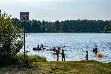 Village of Vysokovo, Ivanovo region, Russia-09.08.2021: Vacationers and bathing people on the shore of Lake Vysokovo on a sunny day, village of Vysokovo, Ivanovo region, Russia. Редакционное
