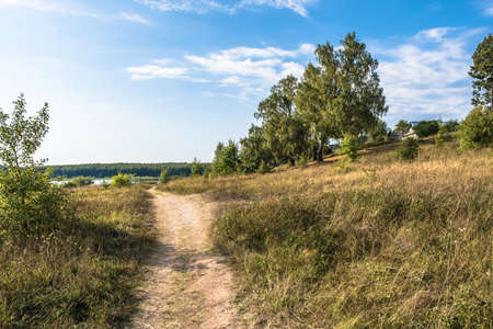 Landscape with a small village on the shore of a lake on a sunny day, Russia.