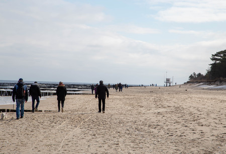 People wandering on the Baltic sea beach of Zempin