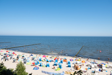 The Baltic sea beach of Koserow with waves and overcast sky and swimming people Standard-Bild - 108716371