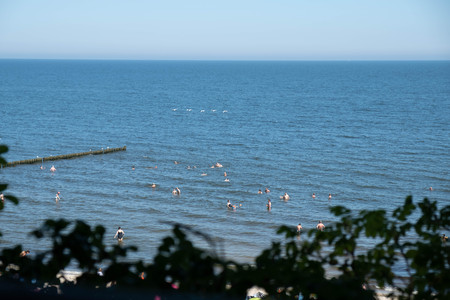 The Baltic sea beach of Koserow with waves and overcast sky and swimming people Standard-Bild - 108716372