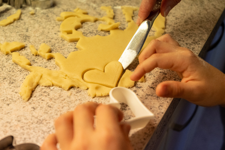 Child shaping and cutting baking cookies for christmas Фото со стока