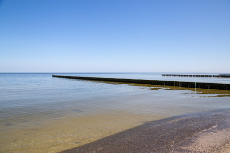 Groynes in the Baltic Sea with small waves in the seaside resort of Zempin on the island of Usedom